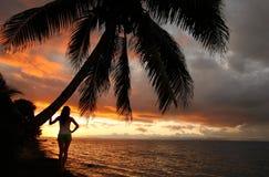 Mujer joven silueteada por la palmera en una playa, Vanua Levu Imagenes de archivo