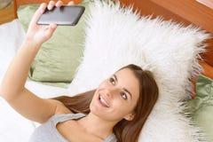 Mujer joven skyping en el teléfono en casa Foto de archivo libre de regalías