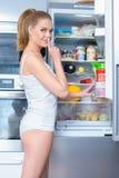 Mujer joven snacking de su refrigerador fotografía de archivo
