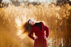 Mujer joven sniling feliz Hembra hermosa con el pelo que sopla sano largo que disfruta de la luz del sol en parque en la puesta d Imagen de archivo