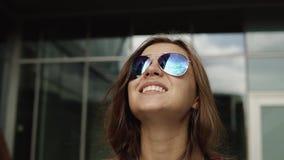 Mujer joven soñada con las gafas de sol marrones del pelo y de la moda cerca del edificio moderno con las paredes del espejo almacen de metraje de vídeo