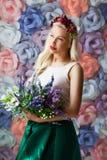 Mujer joven soñadora en la diadema de la flor que se coloca con el ramo de flo Fotografía de archivo