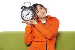 Mujer joven soñolienta con los ojos cerrados en la ropa casera que sostiene el despertador grande imagenes de archivo