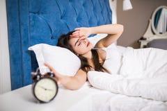 Mujer joven soñolienta de la belleza que estira la mano a la alarma de sonido para apagarla Despierte temprano, no consiguiendo b imagenes de archivo