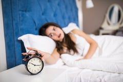 Mujer joven soñolienta de la belleza que estira la mano a la alarma de sonido para apagarla Despierte temprano, no consiguiendo b foto de archivo