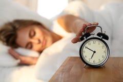 Mujer joven soñolienta que estira la mano a la vuelta dispuesta de sonido de la alarma él apagado Despierte temprano, no consigui fotos de archivo