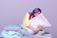 Mujer joven soñolienta que se sienta en cama fotografía de archivo libre de regalías
