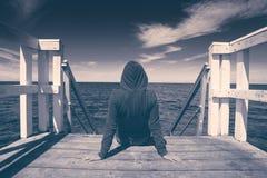 Mujer joven sola en el borde del embarcadero de madera Imagen de archivo