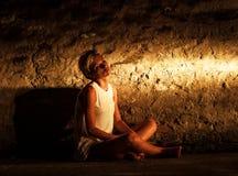 Mujer joven sola que se sienta en la calle Fotos de archivo libres de regalías