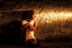 Mujer joven sola que se sienta en la calle Imágenes de archivo libres de regalías