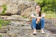 Mujer joven sola que se sienta en rocas Fotografía de archivo