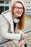 Mujer joven sonriente afuera con los auriculares Foto de archivo