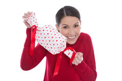 Mujer joven sonriente aislada en el rojo que lleva a cabo un presente con el corazón Fotografía de archivo libre de regalías