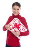 Mujer joven sonriente aislada en el rojo que lleva a cabo un presente en su Han Foto de archivo