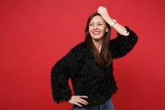 Mujer joven sonriente alegre en el suéter negro de la piel que mira a un lado, guardando la mano en la cabeza aislada en la pared imagen de archivo libre de regalías
