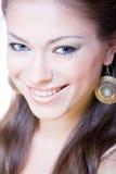 Mujer joven sonriente atractiva con los pendientes Imagen de archivo libre de regalías