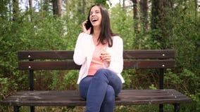Mujer joven sonriente atractiva con smartphone en el parque Resbale el resbalador metrajes