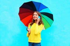 Mujer joven sonriente bonita feliz con el paraguas colorido que habla en smartphone en día del otoño sobre fondo azul colorido Foto de archivo libre de regalías