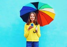 Mujer joven sonriente bonita feliz con el paraguas colorido usando smartphone en día del otoño sobre fondo azul colorido Imagen de archivo