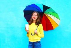 Mujer joven sonriente bonita feliz con la taza de café y el paraguas colorido en día del otoño sobre fondo azul colorido Imagen de archivo libre de regalías