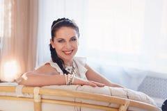 Mujer joven sonriente bonita joven que se sienta en silla del sofá imagen de archivo