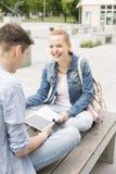 Mujer joven sonriente con el amigo masculino que estudia en banco en el campus de la universidad Imagenes de archivo