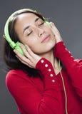 Mujer joven sonriente con el auricular que se relaja al sonido de la música Foto de archivo libre de regalías
