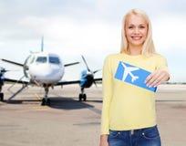 Mujer joven sonriente con el billete de avión Imágenes de archivo libres de regalías