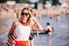 Mujer joven sonriente con el bolso en la playa imagen de archivo libre de regalías