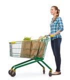 Mujer joven sonriente con el carro de la compra y la comida Fotos de archivo libres de regalías