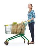 Mujer joven sonriente con el carro de la compra y la comida Foto de archivo libre de regalías