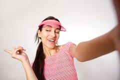 Mujer joven sonriente con el casquillo rosado que toma el selfie Imagenes de archivo