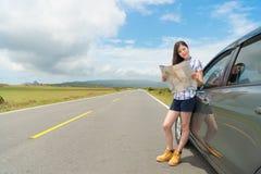 Mujer joven sonriente con el coche en el borde de la carretera del asfalto Foto de archivo