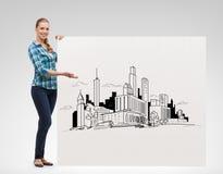 Mujer joven sonriente con el dibujo del tablero y de la ciudad Fotos de archivo libres de regalías