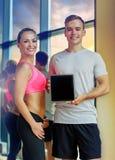 Mujer joven sonriente con el instructor personal en gimnasio imagen de archivo