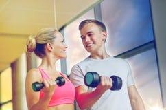 Mujer joven sonriente con el instructor personal en gimnasio fotos de archivo libres de regalías