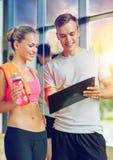 Mujer joven sonriente con el instructor personal en gimnasio fotografía de archivo libre de regalías