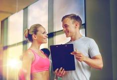 Mujer joven sonriente con el instructor personal en gimnasio foto de archivo