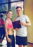 Mujer joven sonriente con el instructor personal en gimnasio fotos de archivo