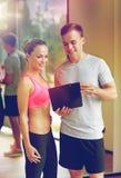 Mujer joven sonriente con el instructor personal en gimnasio imágenes de archivo libres de regalías