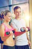 Mujer joven sonriente con el instructor personal en gimnasio imagen de archivo libre de regalías
