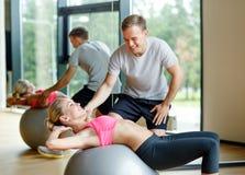 Mujer joven sonriente con el instructor personal en gimnasio Foto de archivo libre de regalías
