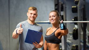 Mujer joven sonriente con el instructor personal en gimnasio imagenes de archivo