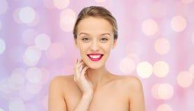 Mujer joven sonriente con el lápiz labial rosado en los labios Fotografía de archivo
