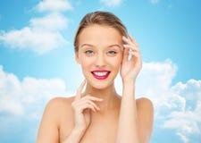 Mujer joven sonriente con el lápiz labial rosado en los labios Fotos de archivo libres de regalías