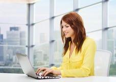 Mujer joven sonriente con el ordenador portátil Fotos de archivo