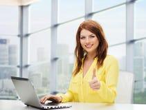 Mujer joven sonriente con el ordenador portátil que muestra los pulgares para arriba Imagenes de archivo