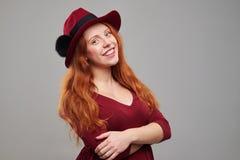 Mujer joven sonriente con el pelo rojo que presenta en sombrero en Fotos de archivo libres de regalías