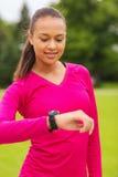 Mujer joven sonriente con el reloj del ritmo cardíaco Fotos de archivo libres de regalías
