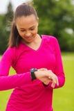 Mujer joven sonriente con el reloj del ritmo cardíaco Imagen de archivo